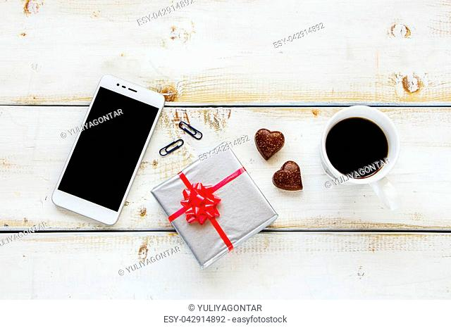Flat lay of coffee break in office workplace with phone, headphones, gift box, coffee cup and chocolate on white wooden background, top view