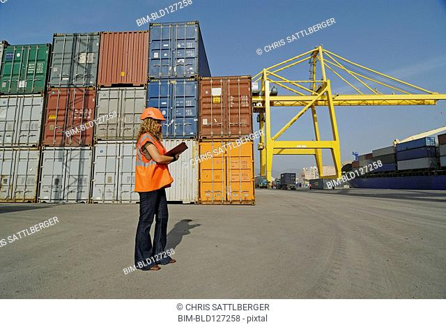Female worker with clipboard in cargo container terminal
