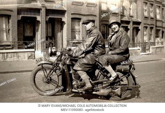 Man & woman on their 1928/9 New Imperial 500cc ohv twin port single motorcycle in the street in the early 1930s