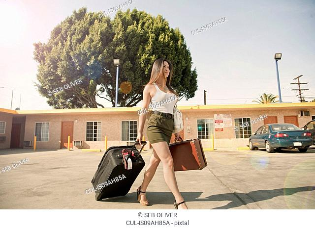 Young woman pulling wheeled suitcase outside motel