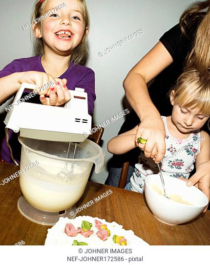 Two girls and a woman baking a cake