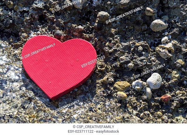 Heart shape on a rocky beach. Summer love abstract