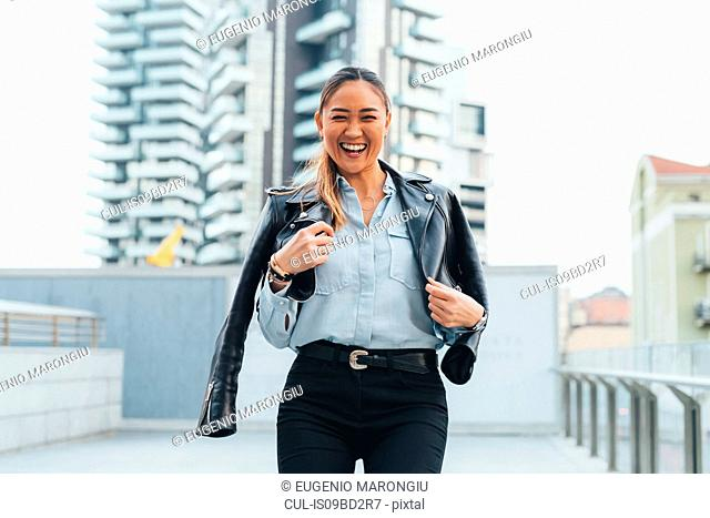Portrait of businesswoman outdoors, wearing leather jacket around shoulders, laughing