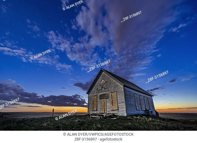 The 1910 Liberty Schoolhouse, a classic pioneer one-room schoolhouse on the Alberta prairie, at sunset as the stars are appearing