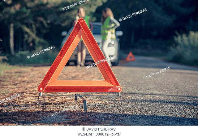Warning triangle in the road by a car breakdown with women in the background