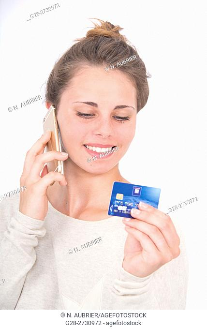 Beautiful young woman using her bank card and telephone to order goods