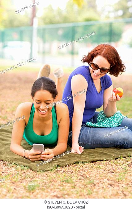 Young women on picnic blanket using smartphone looking down smiling
