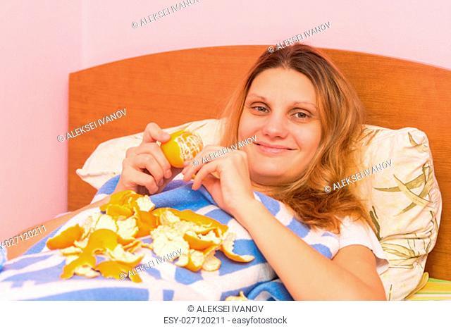 Cheerful girl eats tangerines lying in bed