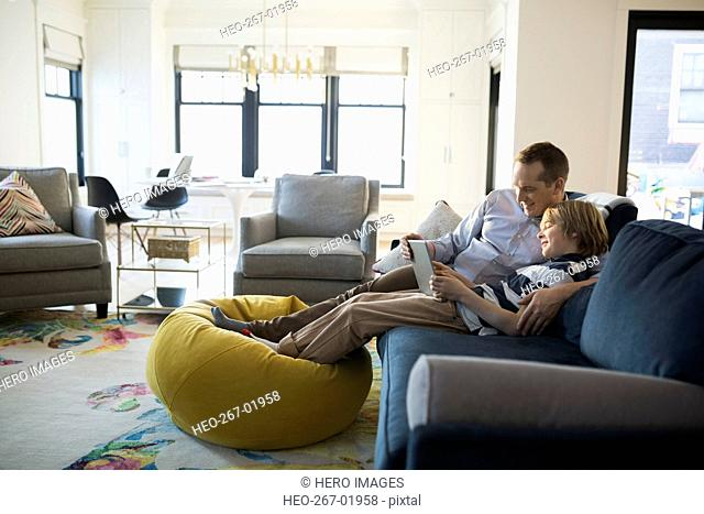 Father son sharing digital tablet living room sofa