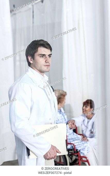 Serious doctor holding file with doctor and patient in background
