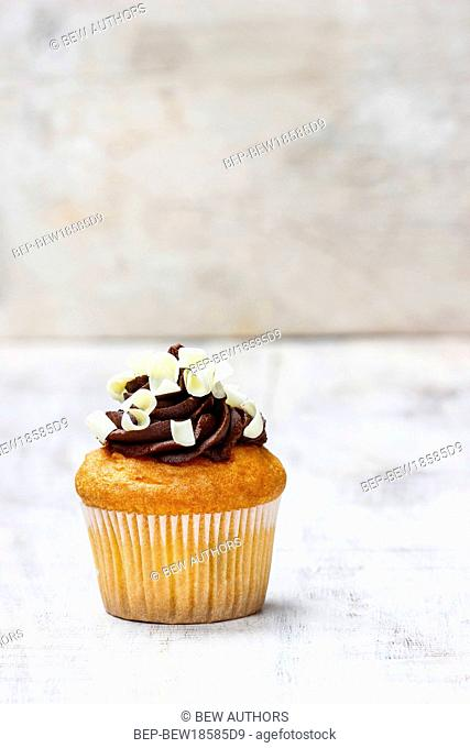 Chocolate cupcake on wooden table. Copy space