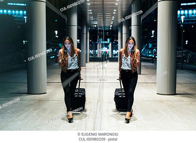 Woman walking beside modern building at night, pulling wheeled suitcase, reflection in window