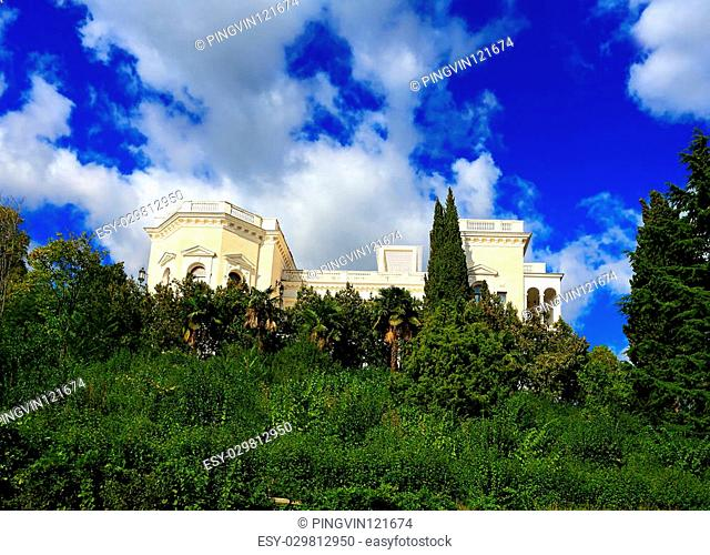 White palace within subtropical cypress trees, pines and palm trees