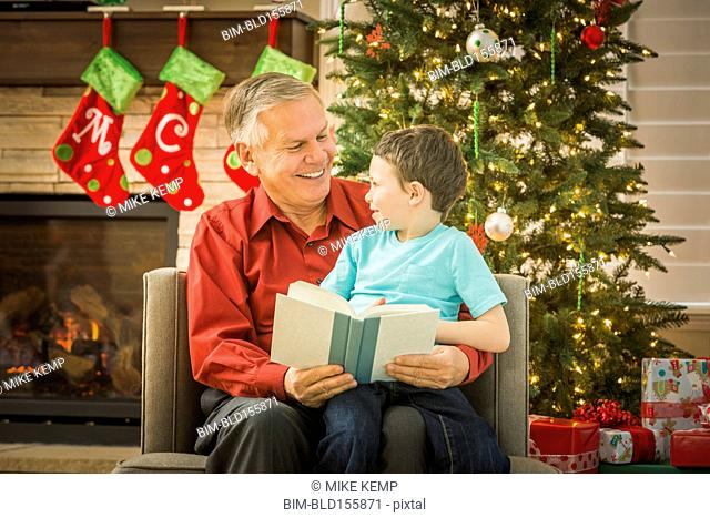 Caucasian grandfather reading to grandson at Christmas