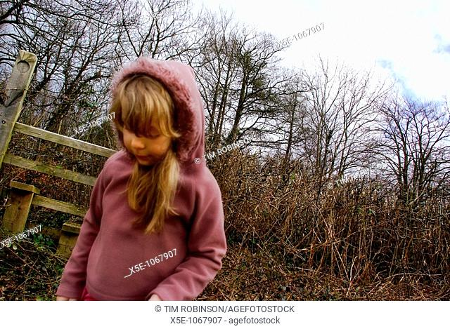 6 year girl looking downwards in rural winter scene