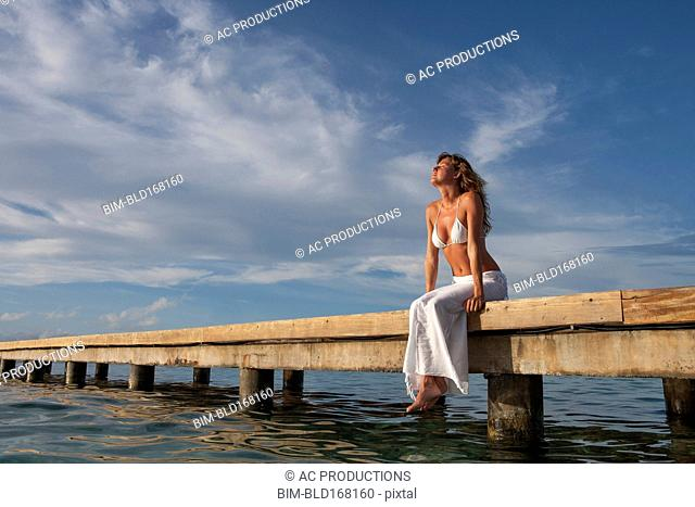 Caucasian woman sitting on wooden dock