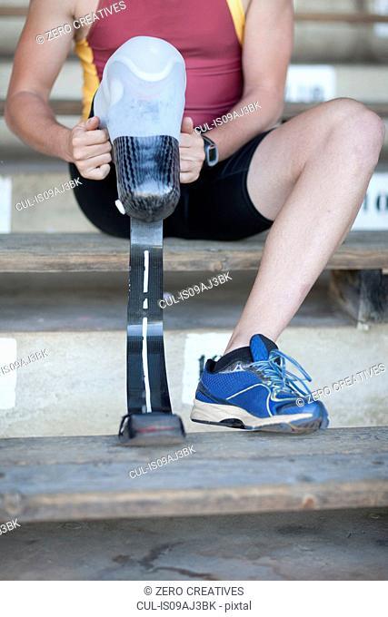 Sprinter preparing, putting on prosthetic leg