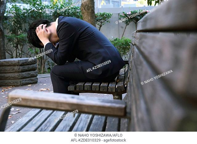 Desperate Japanese young businessman in a suit sitting on a bench in a park