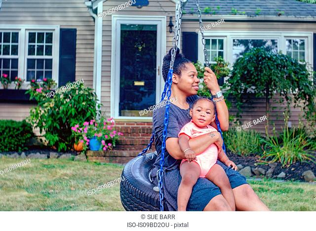 Mid adult woman on garden tire swing with baby daughter