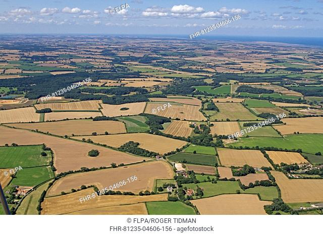 Aerial view of farmland with arable fields, hedgerows and woodland, North Norfolk, England, August