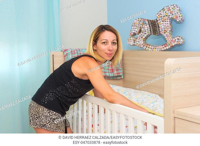 Young woman setting up her baby crib
