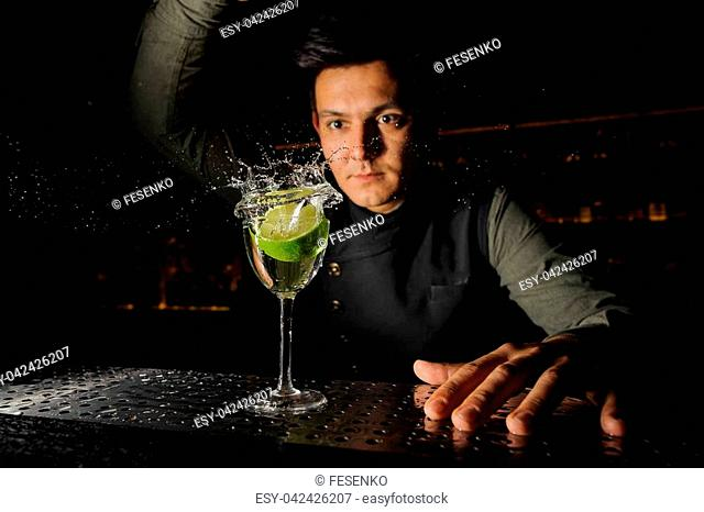 Young barman and a cocktail glass with splashing alcoholic drink and fresh lime in it on the bar counter