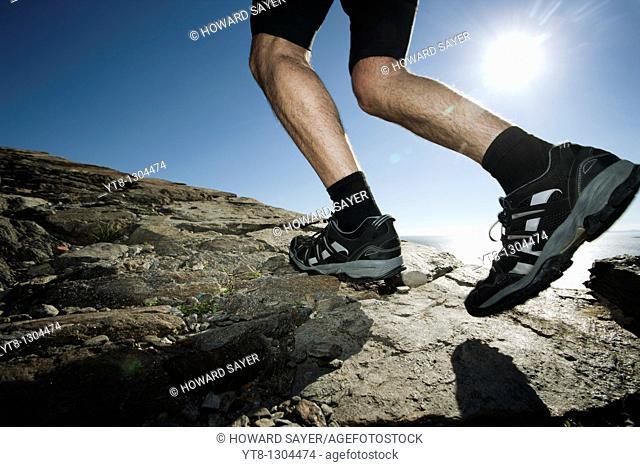 Man running along a rocky coastal path