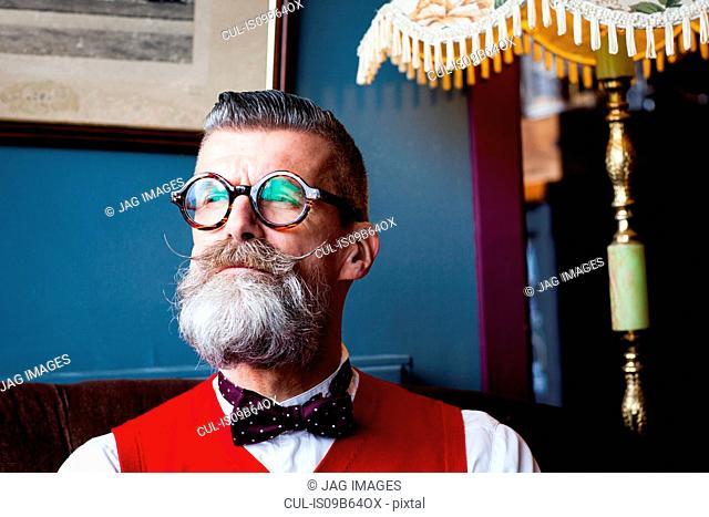 Portrait of stylish quirky senior man vintage cafe