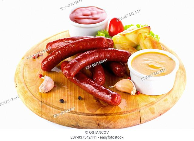 Tasty grilled sausages with vegetables and sauce close up on wooden board isolated on white background