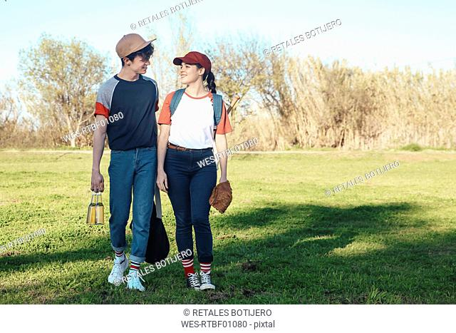 Smiling young couple with baseball equipment walking in park