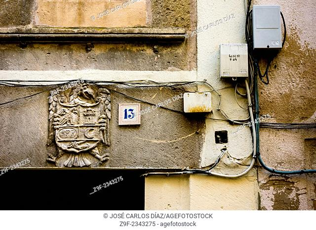 A doorway with crest, wiring and junction boxes (telephone and electricity) in Sepulveda, Segovia, Castilla-Leon, Spain