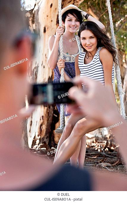 Man taking photograph of two young women sitting on rope swing