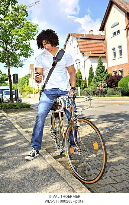 Young male student sitting on a bicycle looking at his smartphone