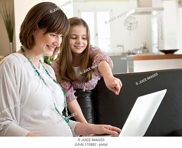 Pregnant mid adult mother and daughter using laptop on sofa