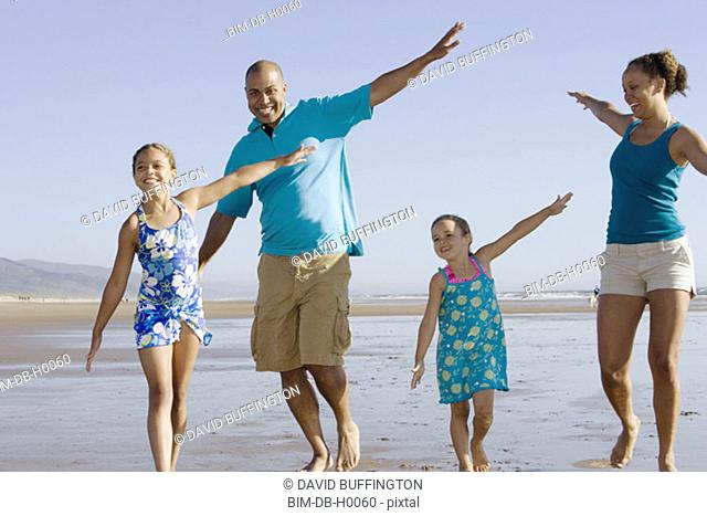 Family playing with arms out at beach