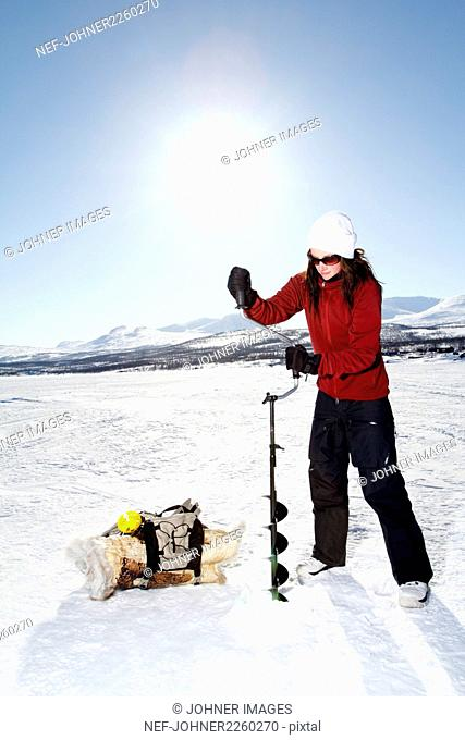 Woman drilling hole in ice