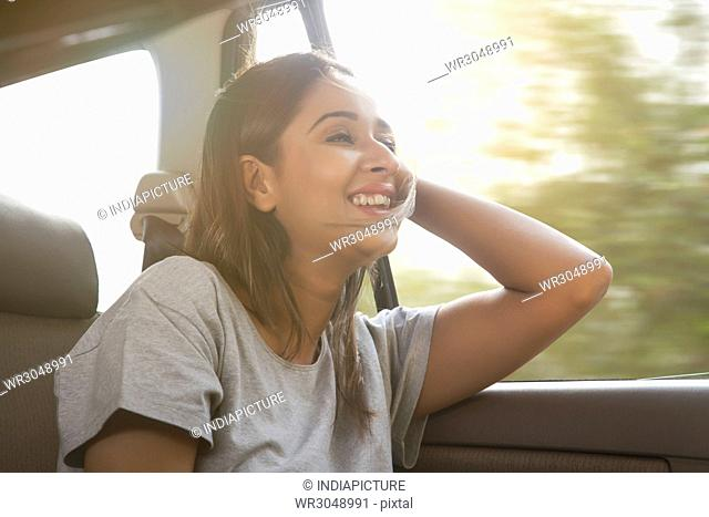 Smiling young women in car hair gets blown by the wind