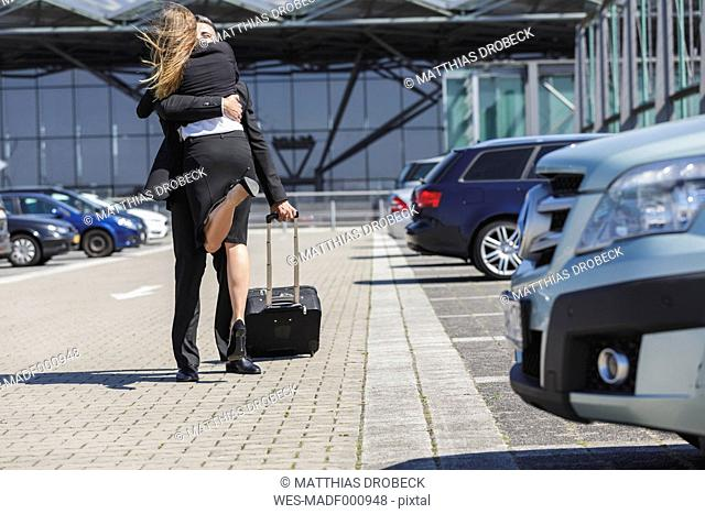 Businessman with luggage at car park hugging woman