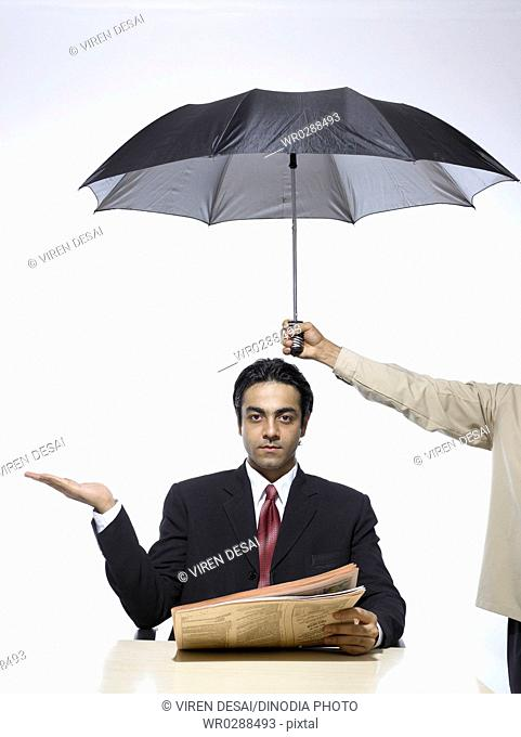 South Asian Indian executive extend hand palm up holding newspaper sitting under umbrella MR702A