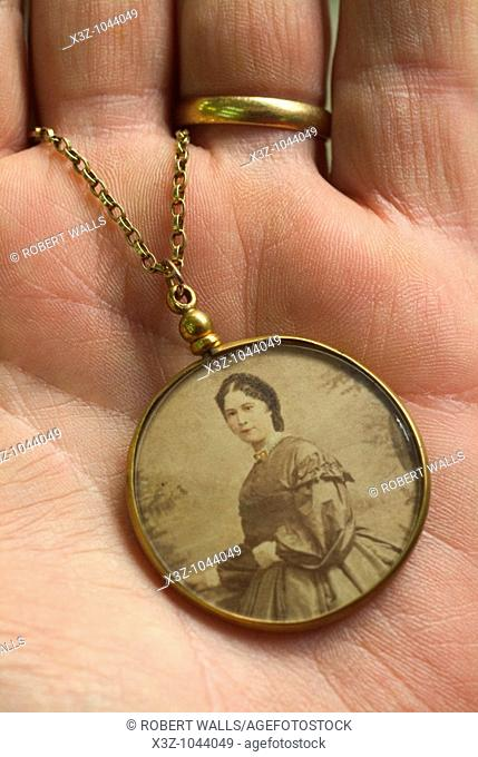 An antique photo frame on a gold chain circa 1860