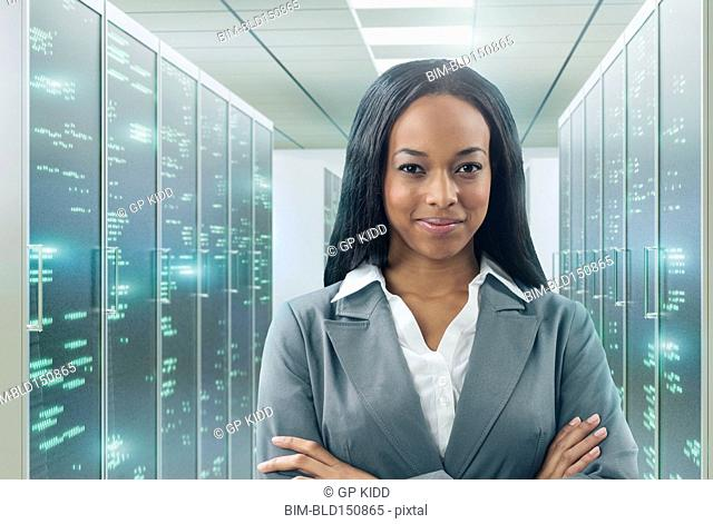 Mixed race businesswoman smiling in server room