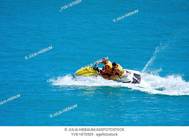 Duo jet skiing in tropical waters