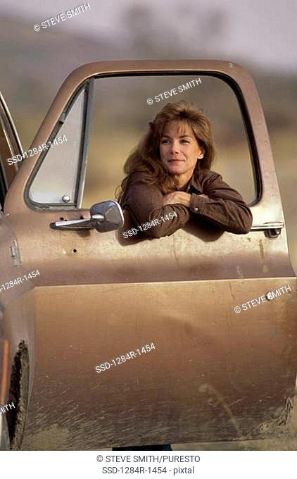 Portrait of a young woman leaning against an open car door