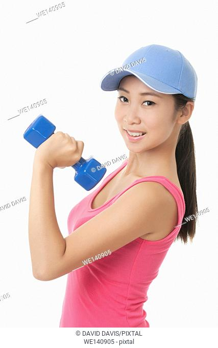 Beautiful Chinese teenager working out using dumbbell weights isolated on a white background