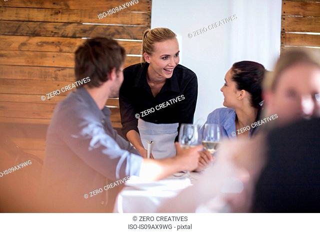 Waitress chatting with customers in restaurant