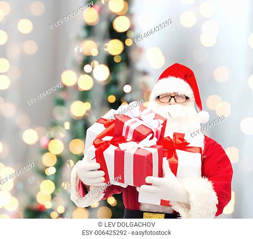 christmas, holidays and people concept - man in costume of santa claus with gift boxes over tree lights background