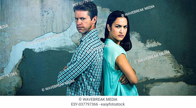 Composite image of portrait of displeased couple standing back to back