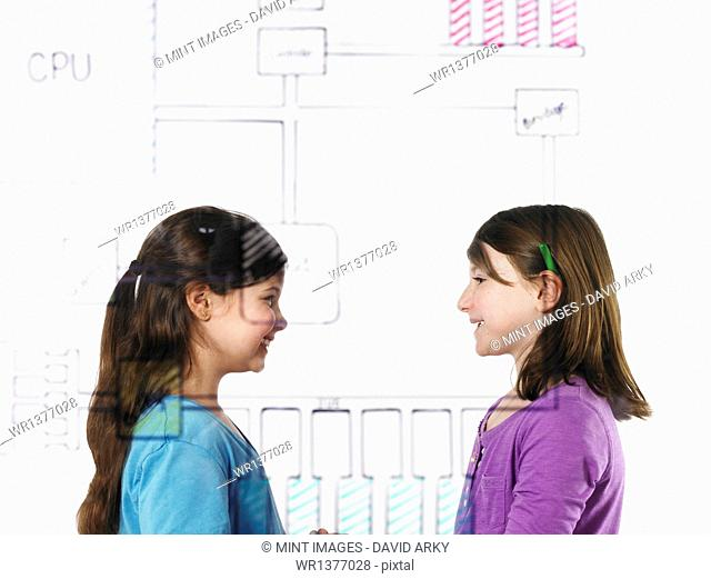 Two children facing each other behind a drawing of a computer motherboard circuit drawn on a see through clear surface