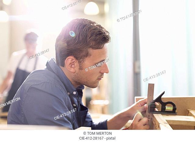 Focused carpenter working in workshop