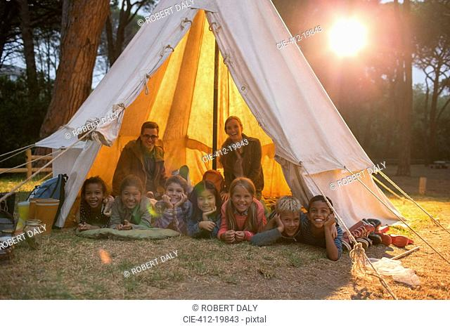 Students and teachers smiling in teepee at campsite